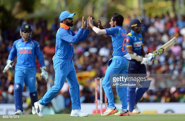 Indian cricketer Yuzvendra Chahal celebrates with his captain Virat Kohli after he dismissed Sri Lankan cricketer Dhanushka Gunathilaka during the...