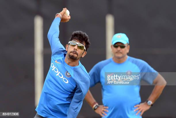 Indian cricketer Yuzvendra Chahal delivers a ball as coach Ravi Shastri looks on during a practice session at the Rangiri Dambulla International...