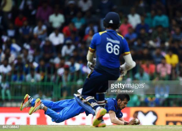 Indian cricketer Yuzvendra Chahal dives to field the ball as Sri Lankan cricketer Lahiru Thirimanne looks on during the final one day international...