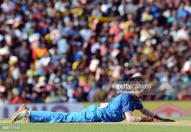 Indian cricketer Yuzvendra Chahal lies on the ground after attempting to field a ball during the first One Day International cricket match between...