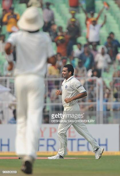 Indian cricketer Zaheer Khan celebrates the dismissal of unseen South African cricketer Hashim Amla during the first day of the second Test match...