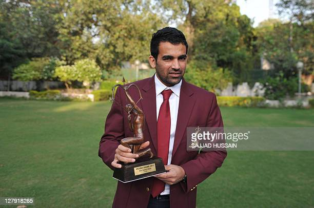 Indian cricketer Zaheer Khan poses with his award after being presented with the Arjun Award 2011 from Indian sports minister Ajay Maken at his...