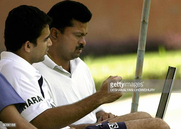 Indian cricketer Zahir Khan watches a video clip on the laptop of team video analyst V. Ramakrishnan during the third and last day of a team...