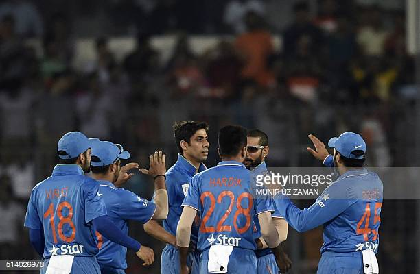 Indian cricketers congratulate teammate Ashish Nehra after the dismissal of the Bangladeshi cricketer Soumya Sarkar during the Asia Cup T20 cricket...