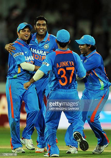 Indian cricketers congratulate teammate Ravichandran Ashwin for taking the wicket of unseen England batsman Ravi Bopara during the first one day...