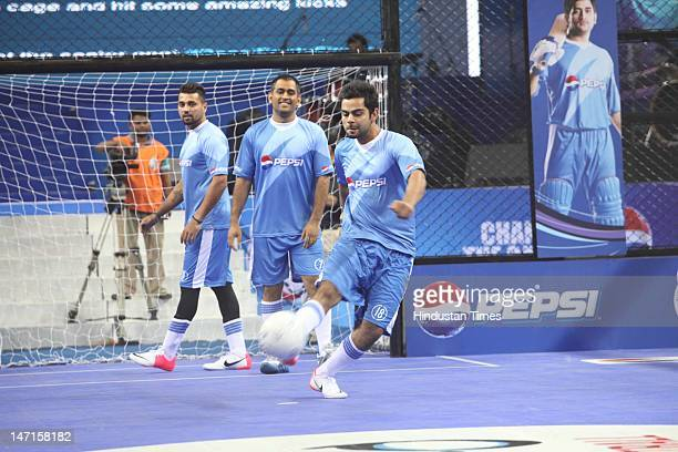 Indian Cricketers Mahendra Singh Dhoni Murli Vijay and Virat Kohli in action during an exhibition indoor football match at the Pepsi T20 Football...