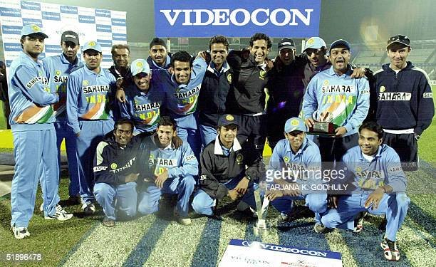 Indian cricketers pose for photographers with their winning trophy following their victory over Bangladesh at the end of the third One Day...