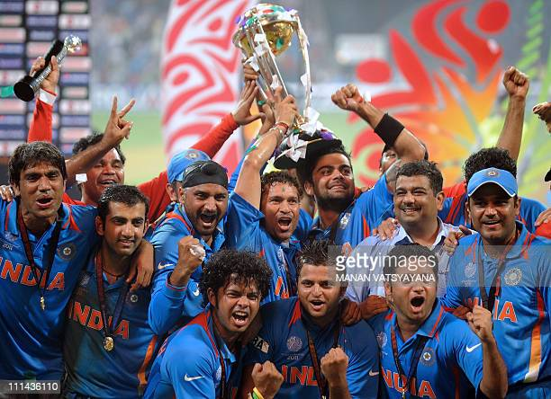 Indian cricketers pose with the trophy as they celebrate after beating Sri Lanka in the ICC Cricket World Cup 2011 final match at The Wankhede...