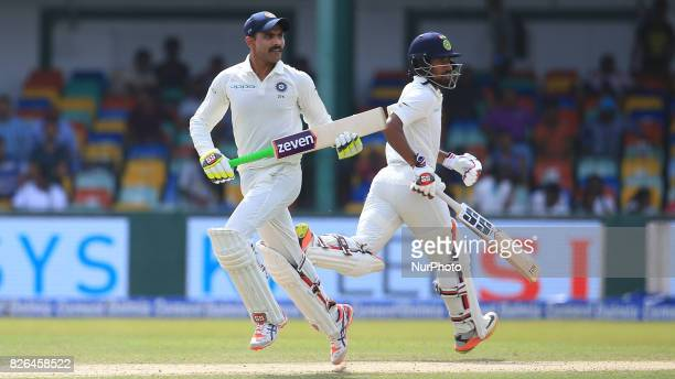 Indian cricketers Ravindra Jadeja and Wriddhiman Saha run between the wickets during the 2nd Day's play in the 2nd Test match between Sri Lanka and...