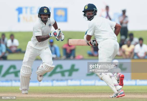 Indian cricketers Shikhar Dhawan and Cheteshwar Pujara run between the wickets during the first day of first Test match between Sri Lanka and India...
