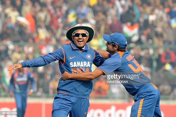 Indian cricketers Virender Sehwag and Suresh Raina celebrate the dismissal of unseen Sri Lankan batsman Thilan Samaraweera during the fifth and final...