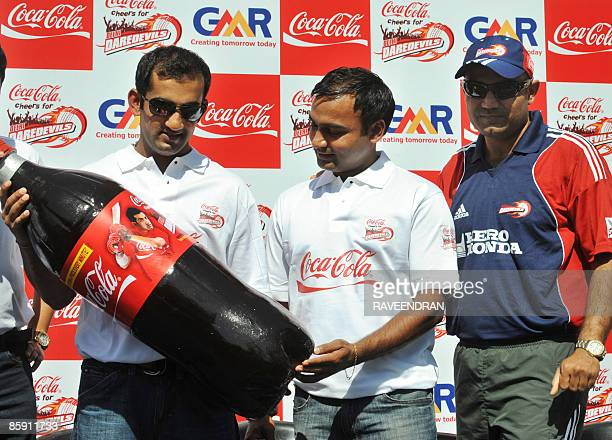 Indian cricketers Virender Sehwag Gautam Gambhir and Amit Mishra unveil an oversized limited edition CocaCola bottle during a sponsored sendoff event...