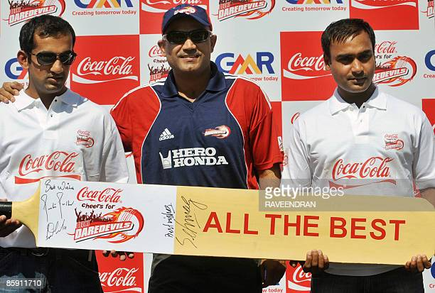 Indian cricketers Virender Sehwag Gautam Gambhir and Amit Mishra pose with a giant cricket bat during a sponsored sendoff event for the Indian...