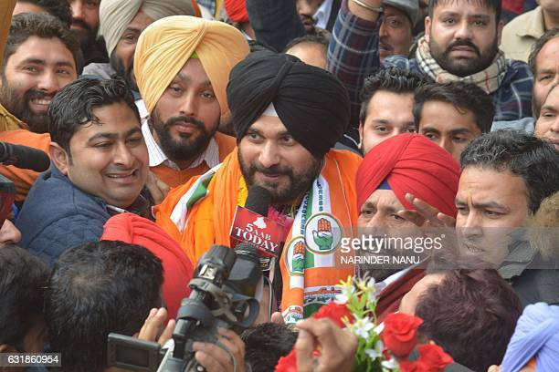 Indian cricketer-turned-politician and former member of parliament Navjot Singh Sidhu is surrounded by supporters after announcing he has joined the...