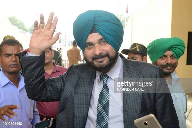 Indian cricketerturnedpolitician and Punjab cabinet minister Navjot Singh Sidhu waves after crossing the IndiaPakistan border in Wagah about 35km...