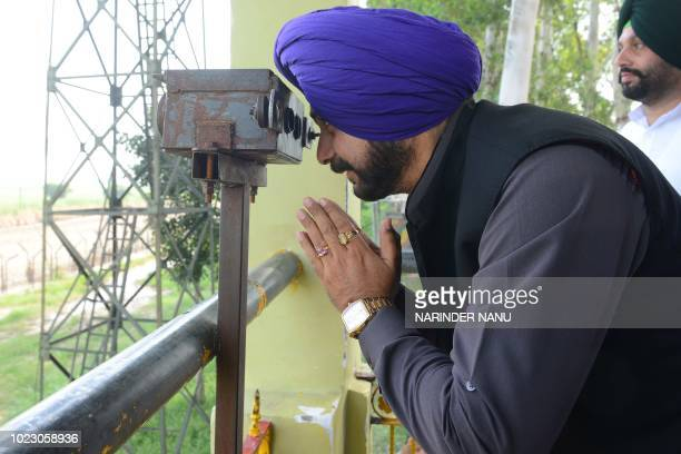 Indian cricketerturnedpolitician and Punjab cabinet minister Navjot Singh Sidhu gestures after offering prayers for his proposal on opening a...