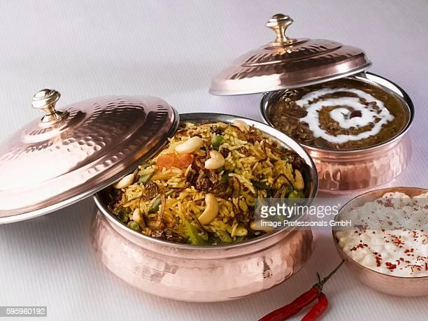 indian cuisine: biryani (rice dish), dal makhani (lentil dish), boondi raita (chick-pea balls in yoghurt sauce) - biryani stock photos and pictures