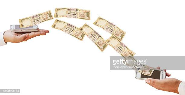 Indian currency flowing from mobile phones over white background