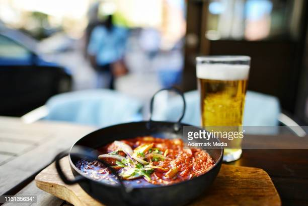 indian curry dish & beer on an outdoor table - curry meal stock photos and pictures