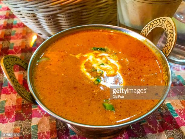 Indian curry served in copper bowl on table