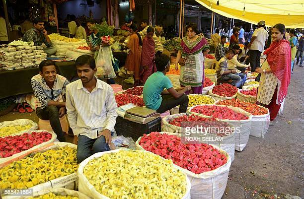 Indian customers buy flowers at a wholesale flower market in Hyderabad on August 3 2016 Finance Minister Arun Jaitley said India was on the cusp of...