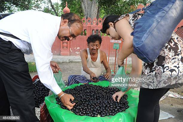 Indian customers buy jamun fruit at a roadside stall in Amritsar on July 6 2011 Jamun a popular seasonal fruit comes from an evergreen tropical tree...