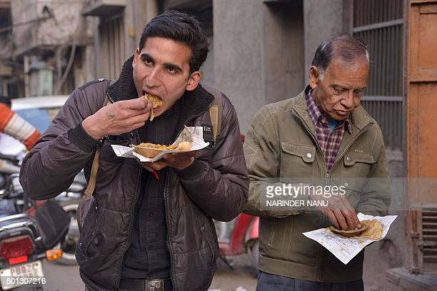 Indian customers eat poori or puri - fried puffed whole wheat flat bread - and channa or chole masala - chickpeas - at a 56 year-old shop in Amritsar...
