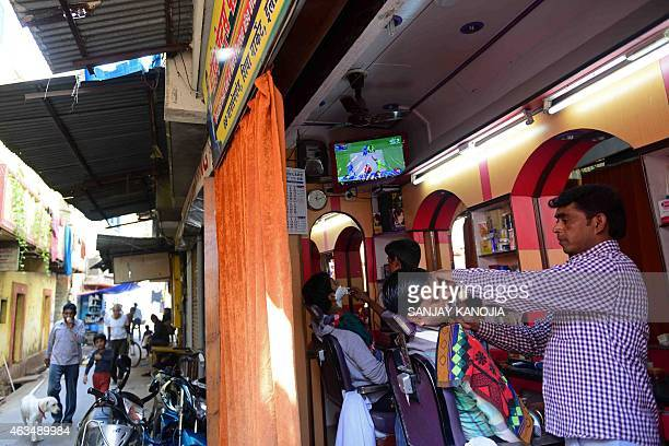 Indian customers get a shave at a barbershop at a television shows a live broadcast of the Cricket World Cup match between India and Pakistan in...