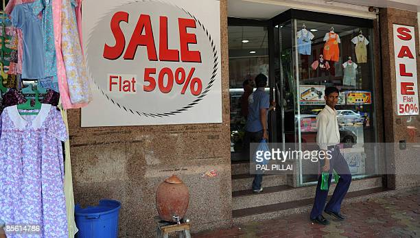 Indian customers leave a shop adorned with sale signs in Mumbai on March 26, 2009. Inflation in India edged closer to zero, official data showed,...