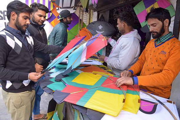 Indian customers look at kites on display at a kite shop in Amritsar on January 11 2016 The demand for kites is rising ahead of the Lohri harvest...