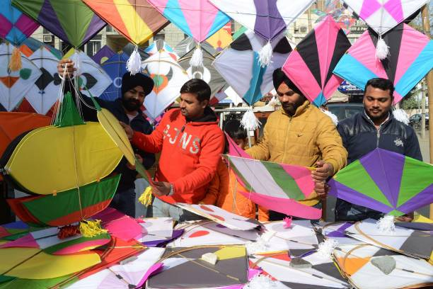 Indian customers look at kites on display at a kite shop in Amritsar on January 10 2018 The demand for kites is rising ahead of the Lohri harvest...