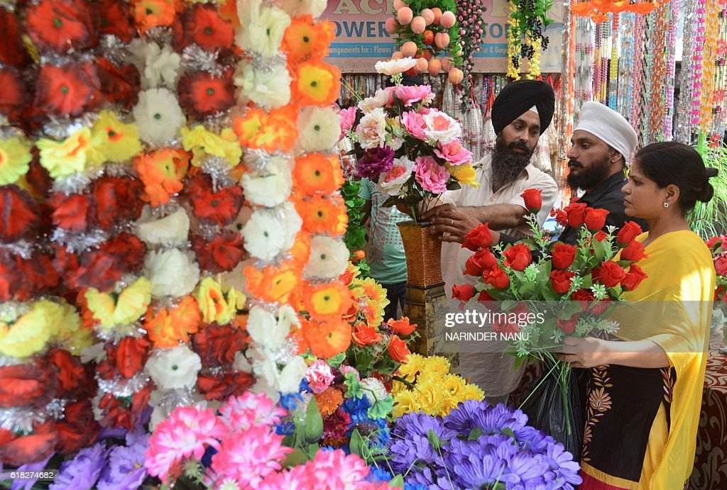 Indian customers pose for a photograph as they are served by a vendor selling artificial flowers at a shop ahead of the Hindu festival of Diwali in...