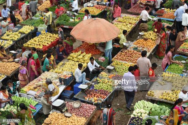 Indian customers shop and a fruit and vegetable market in Ahmedabad on July 12 2017 / AFP PHOTO / SAM PANTHAKY
