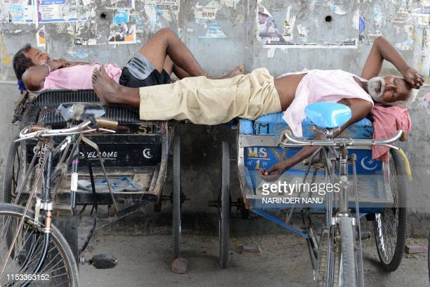 Indian cycle-rickshaw drivers take a nap under a flyover bridge during a hot summer day in Amritsar on July 3, 2019.