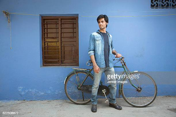 Indian cyclist standing in city street.