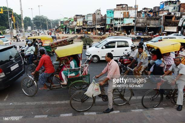Indian cyclist Sushil Kumar holds onto the bars of his bicycle as he joins other commuters in cars buses auto rickshaws and motor bikes at a traffic...