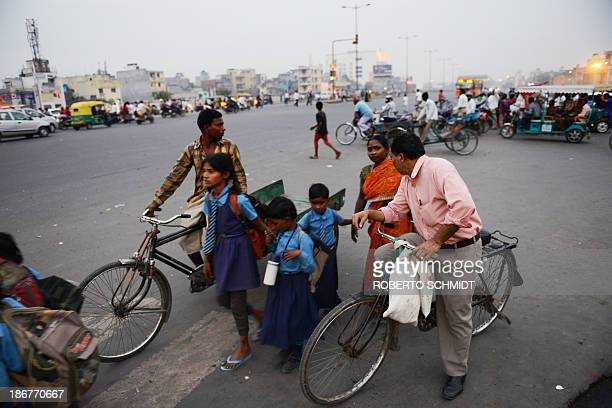 Indian cyclist Sushil Kumar pauses at an intersection in New Delhi on November 1 as he returns home from work Trucks and buses often driven with...