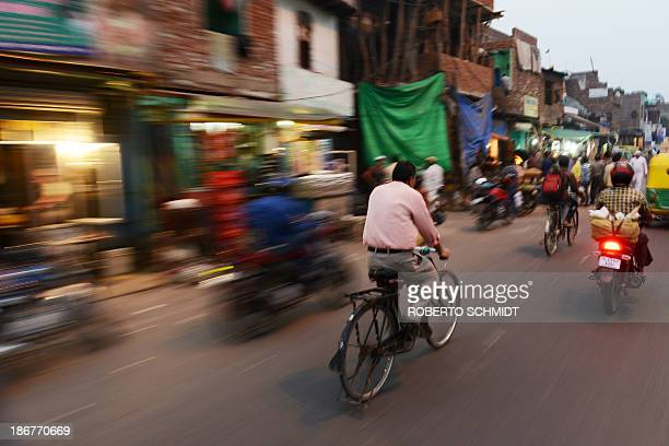 Indian cyclist Sushil Kumar rides past a roadside market in New Delhi on November 1 as he returns home from work Trucks and buses often driven with...