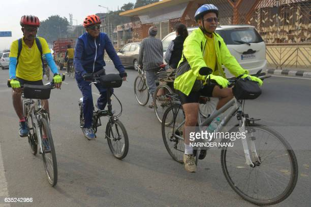 Indian cyclists Jugal Kishore Rajesh Sharma and Raj Mhatre ride along a road in Amritsar on February 14 during their journey from the IndiaPakistan...