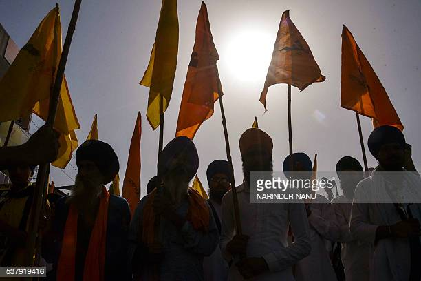 Indian Dal Khalsa Sikh organisation activists hold flags and placards during a protest march ahead of the 32nd anniversary of Operation Blue Star in...