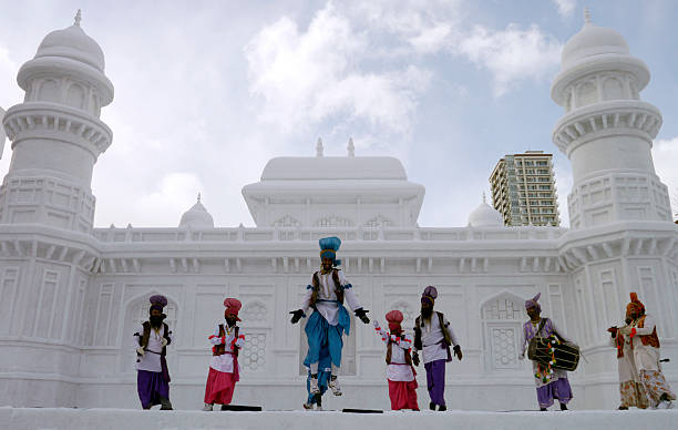 Indian dancers perform a Bhangra dance at the stage in front of the large snow sculpture of `Tomb of ItmadudDaula` of India during the 65th annual...