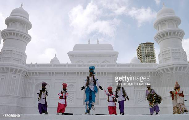 """Indian dancers perform a Bhangra dance at the stage in front of the large snow sculpture of """"Tomb of Itmad-ud-Daula"""" of India during the 65th annual..."""