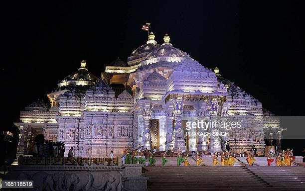 Indian dancers perform a routine in front of The Swaminarayan Akshardham Temple during its inauguration ceremony in New Delhi 06 November 2005 The...