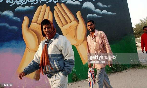 Indian day laborers walk past a mosque March 4, 2003 in Fuhayhil, Kuwait. Fuhayhil is the boyhood home of Khalid Shaikh Mohammed, the al Qaeda leader...