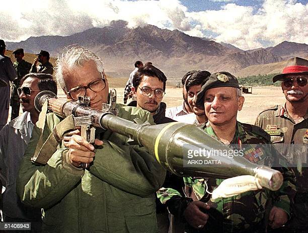 Indian defence minister George Fernandes takes aim through a shoulder held grenade launcher which was confiscated from the posts held by the Moslem...