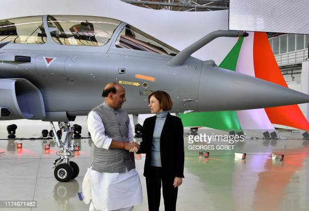 Indian Defence minister Rajnath Singh shakes hands with French Defence Minister Florence Parly during the ceremony marking the delivery of the first...