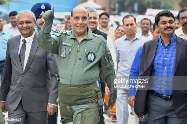 Indian Defence Minister Rajnath Singh waves to onlookers as Hindustan Aeronautics Limited Chairman R Madhavan and Defense Research and Development...