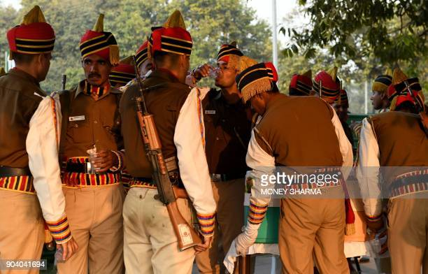 Indian Delhi police personnel drink water as they take a