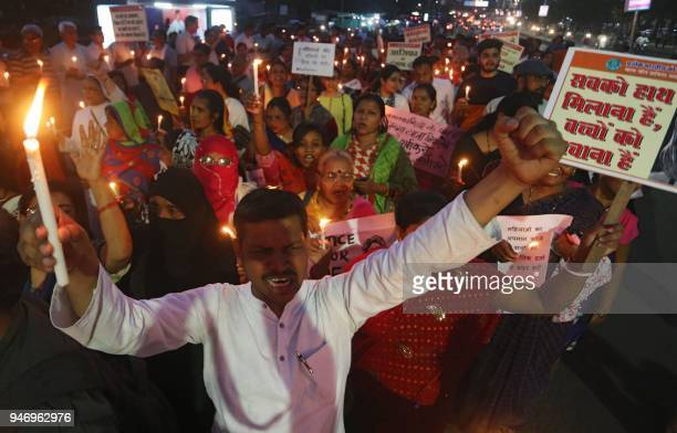 Indian demonstrators and NGO members hold placards and lit candles during a protest against the recent rape cases in Uttar Pradesh and Jammu and...