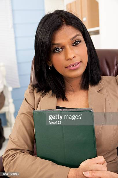 Indian descent business woman in office setting. Portfolio.